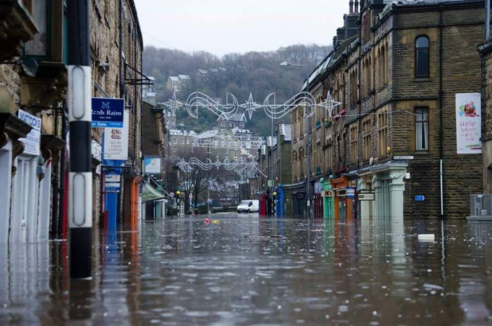 2 Tone Comics in Hebden Bridge (the orange-coloured shop on the right hand side of this photograph) was one of many businesses devastated by recent floods, along with thousands of home owners across the North of England and Scotland. Photo: 2 Tone Comics