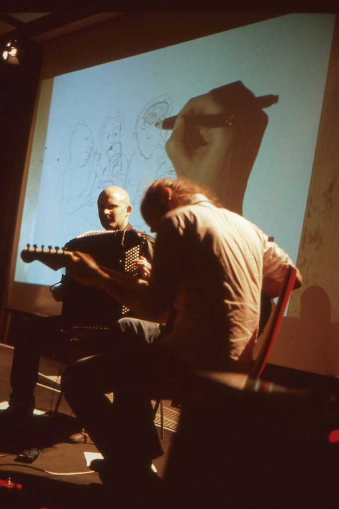 On stage: Ville Ranta, illustration; Aleksi Ranta, guitar; Niko Kumpuvaara, accordion.