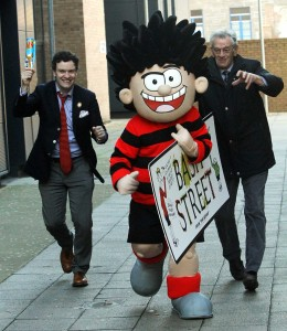 Dennis makes off with a copy of the Bash Street sign, pursued by Mike Stirling an veteran Beano artist Dave Sutherland.