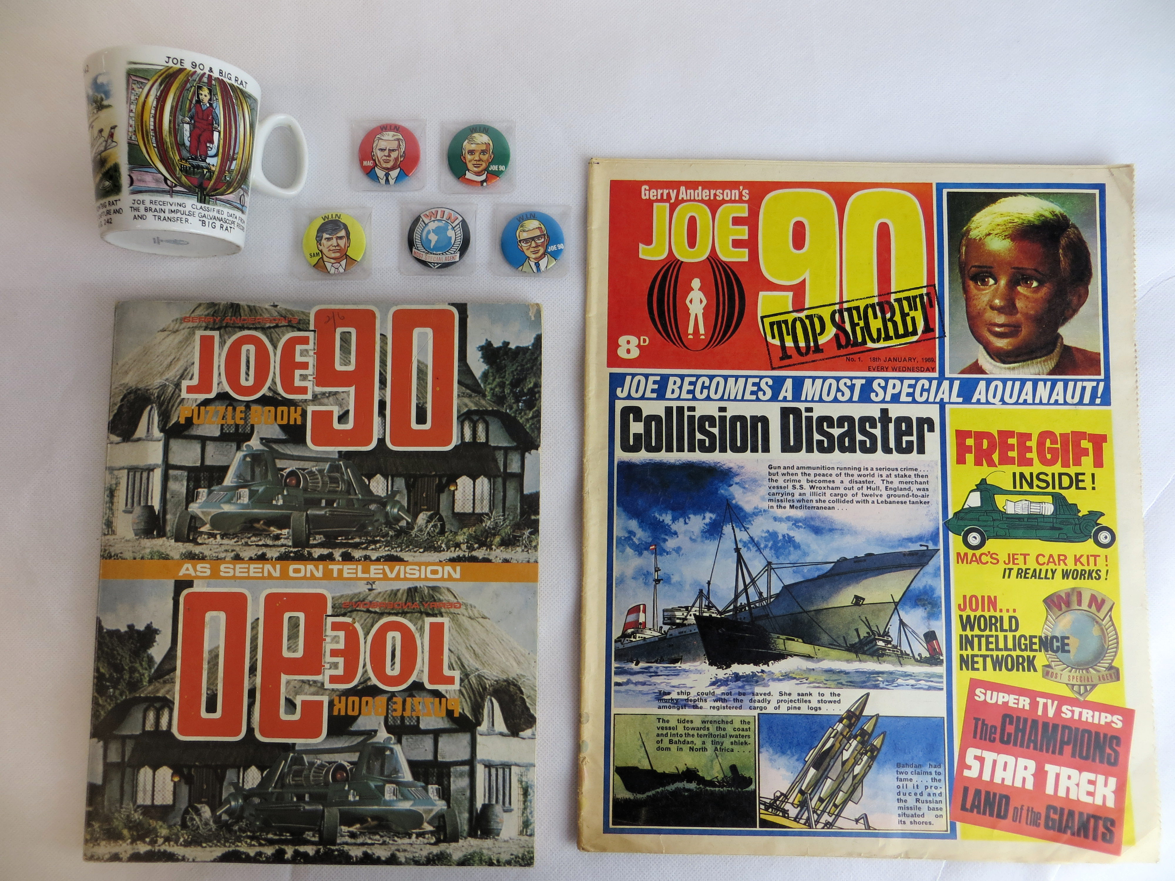 Joe 90 Comic Number One, published in 1969, with Joe 90 puzzle book, Washington pottery mug and badges, being offered at auction in Cardiff today by Langley and Jones