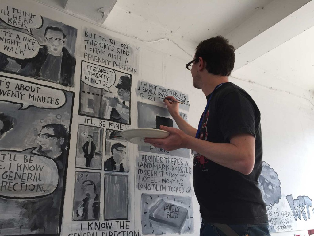 """Comic artist Joe Decie at work on his """"Lost in Kendal"""" mural during the Festival weekend, one of many commissioned projects to bring comics to Kendal's high street, Angouleme Festival style, as well as comic fans. Photo: John Freeman"""