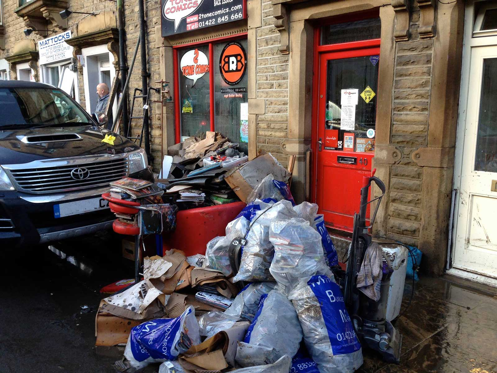 After the storm: clean up work begins at 2 Tone Comics, Hebden Bride. Fand and friends of the independent comic shop have rallied to help raise funds to get the owners, who were unable to insure the shop after previous flooding, back on its feet. Photo: 2 Tone Comics