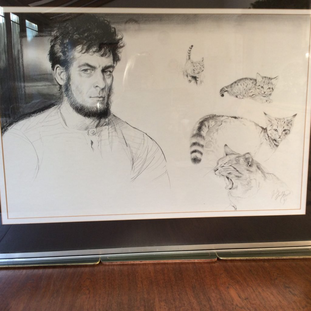 """An illustration of author Mike Tomkies, """"The Wilderness Man"""", and his wild cat Kitten, painted by Shirley in 1981. As well as being a writer Mike, who lived on Loch Shiel and he and Shirley were great friends. She illustrated some, if not all, of his books describing his life in the wilds of Scotland. He died in October 2016."""