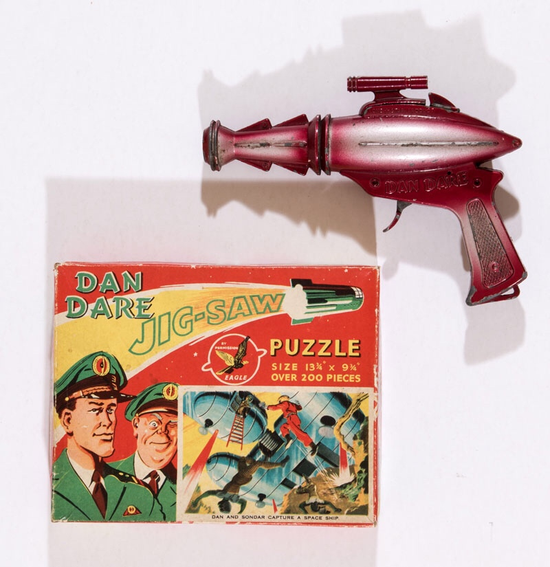 A Dan Dare Space Pistol (produced in the 1950s by Lone Star). The trigger action is in full working order, although there's some wear and paint chips. Offered with a boxed Dan Dare Jigsaw Puzzle and a lapel badge.